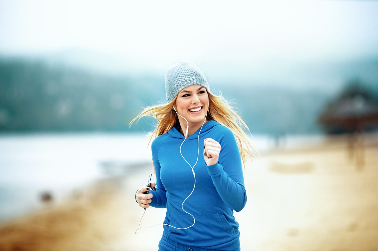 Young blonde woman is jogging and listening music on the beach.