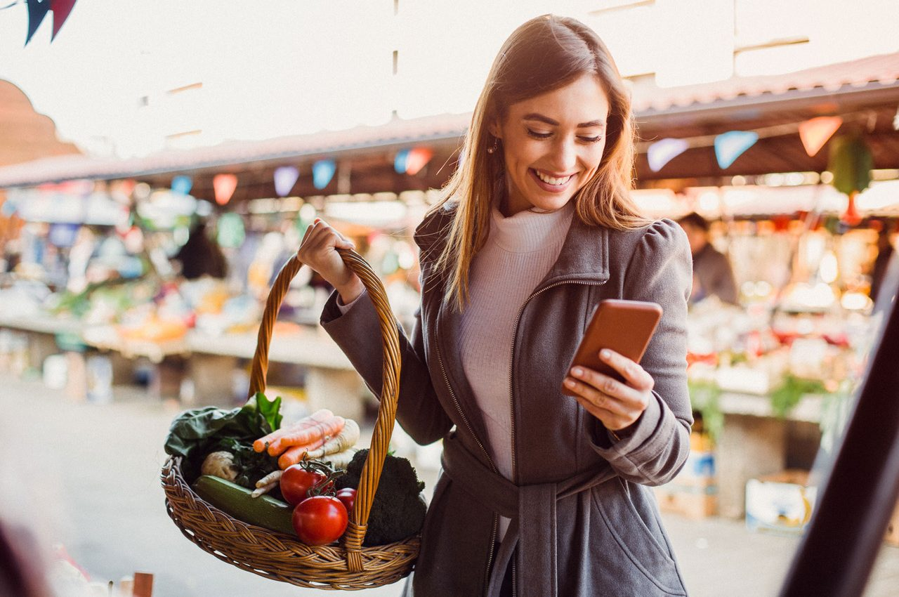 Beautiful young brunette text messaging on her smart-phone while she's doing shopping at farmers' market.