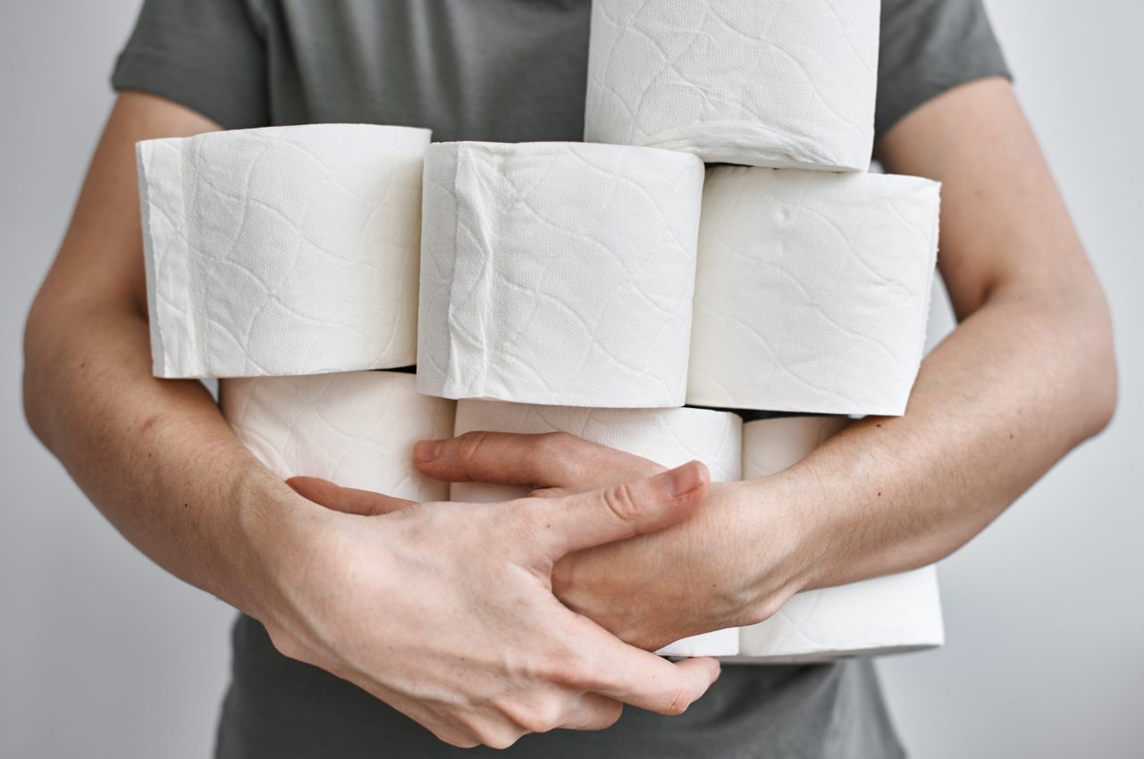 People are stocking up toilet paper for home quarantine from crownavirus. Woman holds many rolls of toilet paper